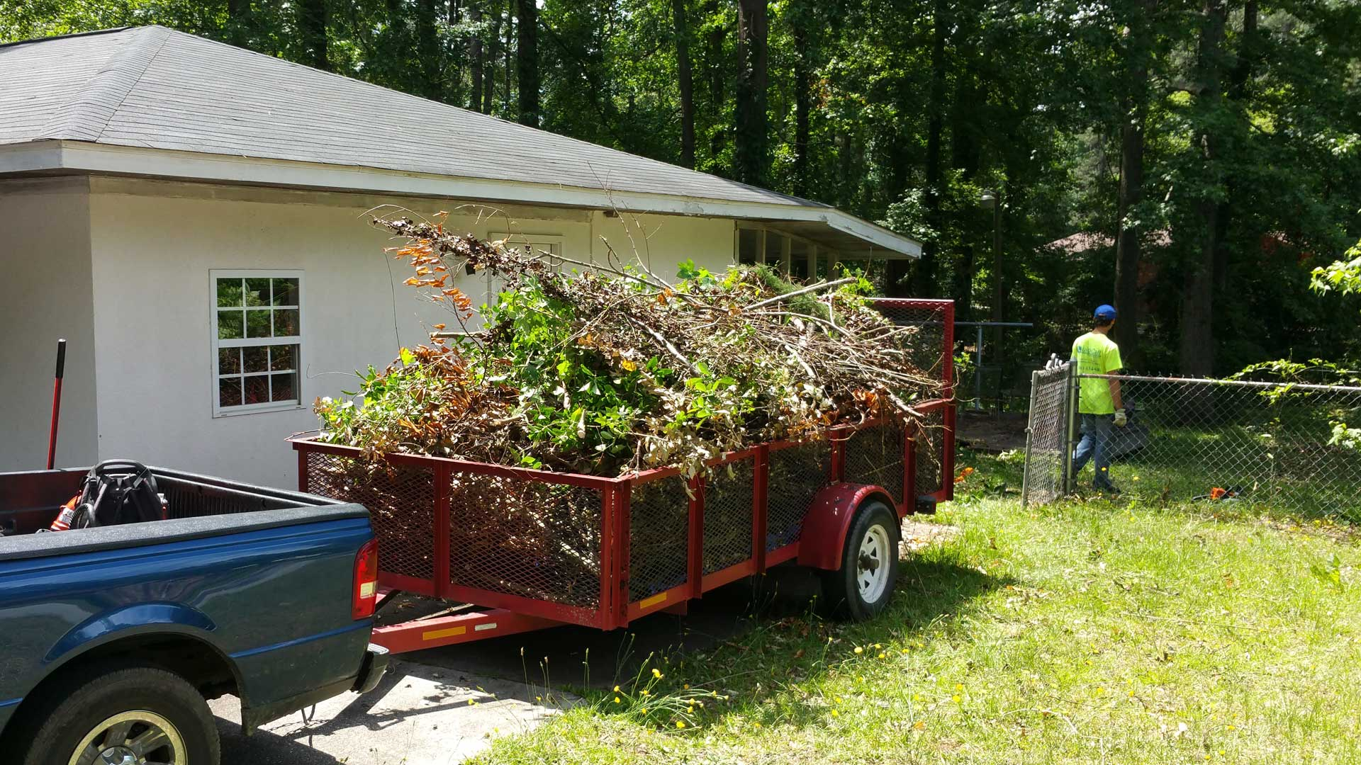 QuickCall Services removing overgrown landscape debris from a home in Martinez, GA.