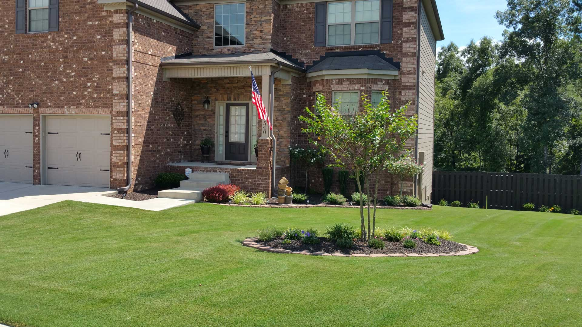 Perfectly trimmed shrubs and bushes at a home in Evans with frequent landscape maintenance.