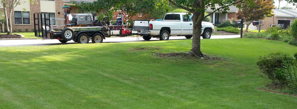 QuickCall Services truck and lawn equipment beside a recently mowed lawn in Grovetown